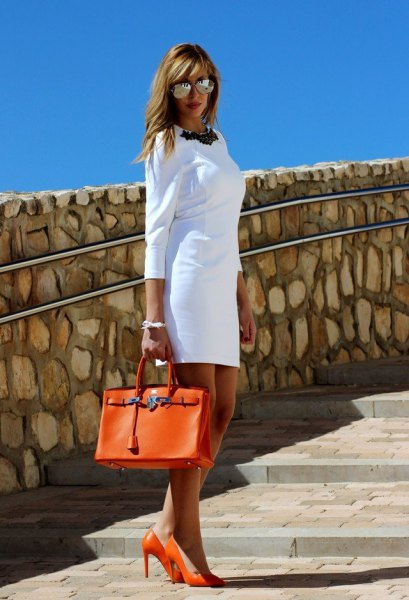 white three-quarter sleeved mini shift dress with orange leather case