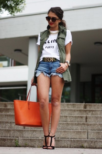 white print tee with olive green vest and denim mini-shorts