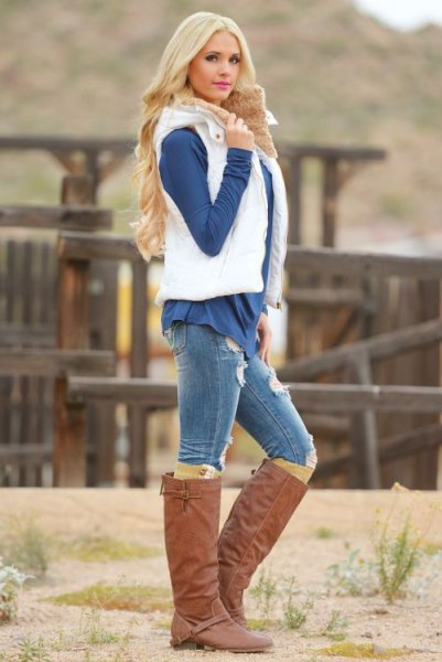 white puffer vest with navy blue blouse and brown knee high boots