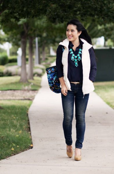 white puffer vest with back-up shirt and dark blue skinny jeans
