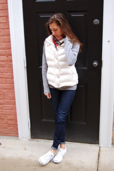 white puffer vest with gray long sleeve tee and dark blue cuffed jeans