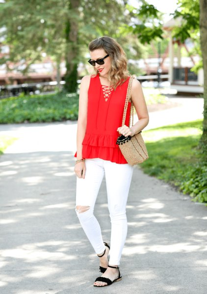 red criss cross front v-neck sleeveless blouse with white ripped jeans