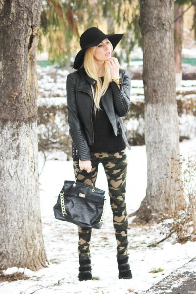 black leather jacket with skinny camo jeans and floppy hat