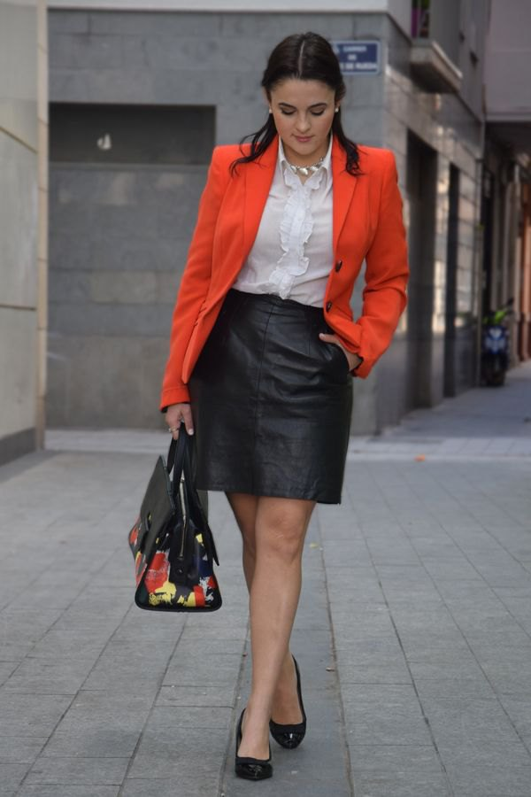 best orange jacket with white ruffled blouse and mini skirt in black leather