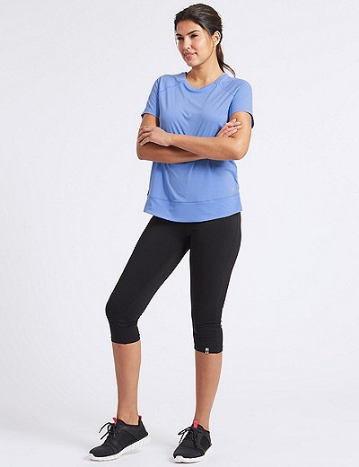 light blue t-shirt with black short leggings and sneakers