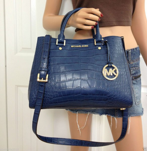 navy blue leather bag with green crop top and mini shorts