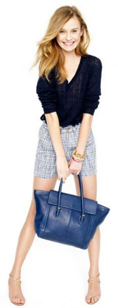 black shirt with gray checkered liquid shorts and navy leather handbag
