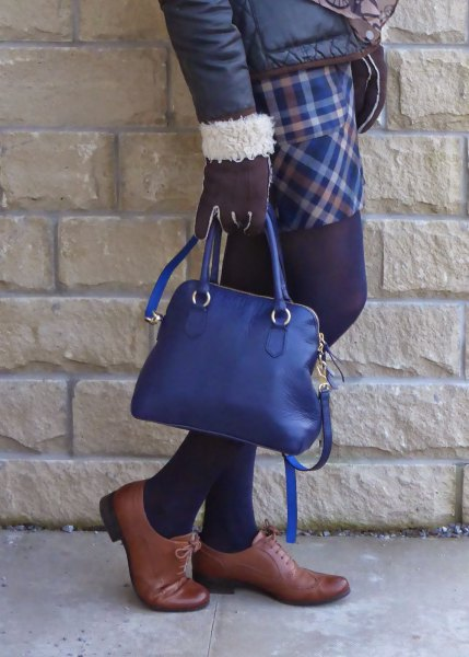 black down jacket with plaid skirt and deep blue handbag