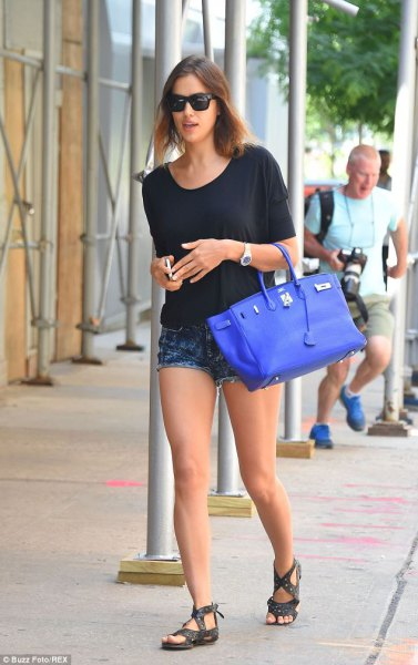 black t-shirt with dark denim shorts and royal blue leather bag