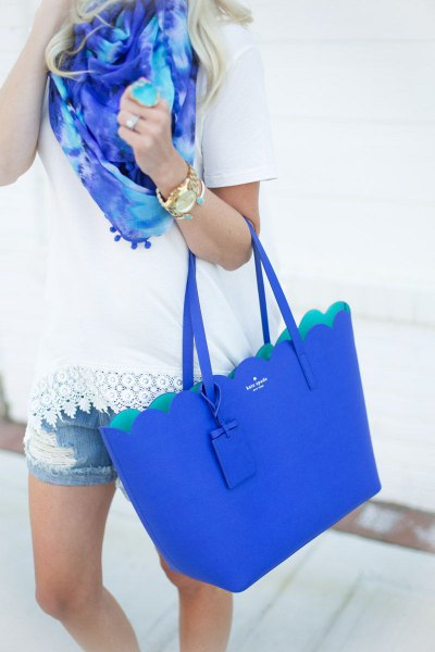 white crochet tee with denim shorts and royal blue handbag