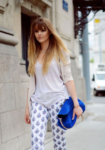 gray sweater with scoop neck with white printed trousers and royal blue suede bag