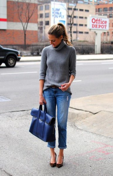 gray turtleneck knit sweater with blue cuffed jeans and matching portfolio