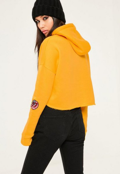 mustard yellow cropped hoodie with black jeans in high waist