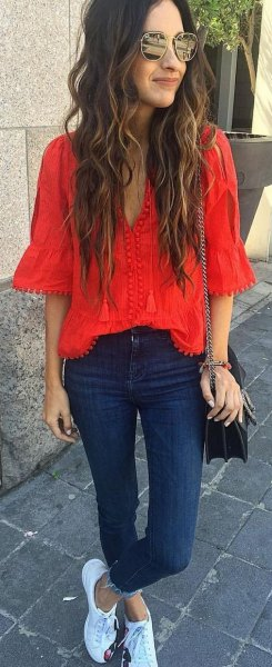 red watch sleeve v-neck blouse with dark blue skinny jeans