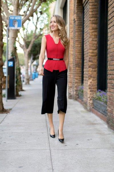 red sleeveless belt blouse with black cropped trousers with straight legs