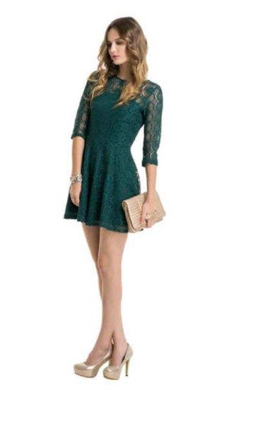 dark green dress with light pink clutch bag
