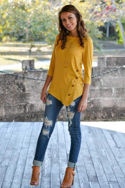 mustard yellow t-shirt with three sleeves with cuffed ripped jeans
