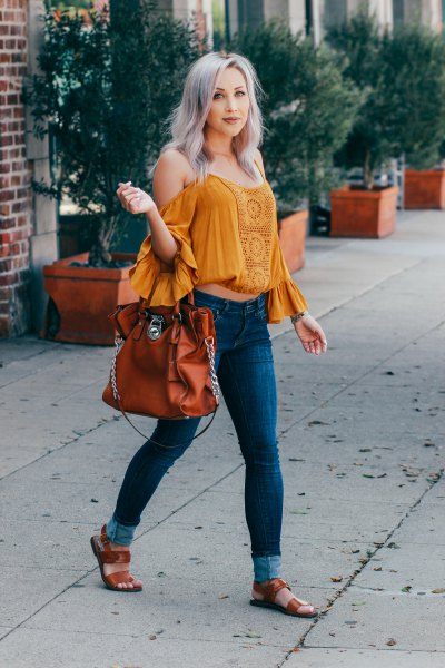 mustard off the shoulder ruffle sleeve crop top with blue skinny jeans