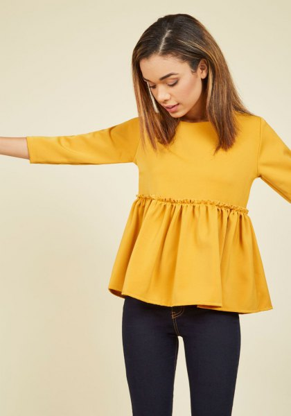 mustard yellow long sleeve peplum top with black skinny jeans
