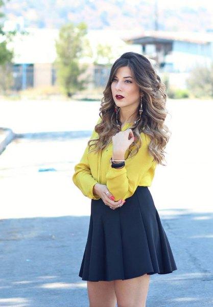 mustard button up blouse with black high waist skate skirt