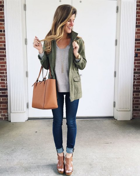 olive jacket with gray sweater and cuffed dark blue skinny jeans