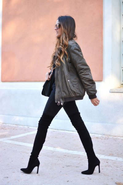 gray bomber jacket with black jeans and mid calf boots