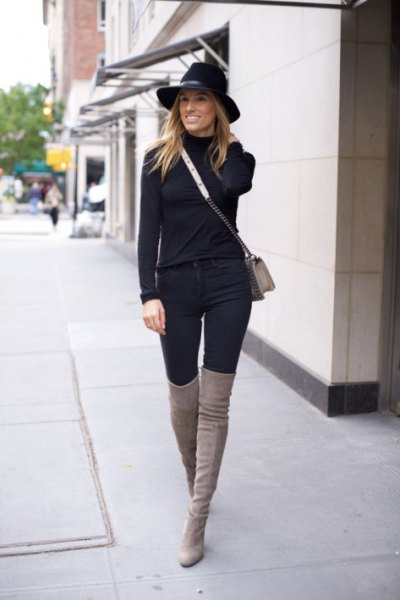 black sweater with matching high jeans and high boots in gray thighs