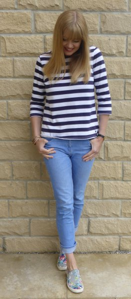 black and white three-quarter sleeved tee with light blue features on skinny jeans