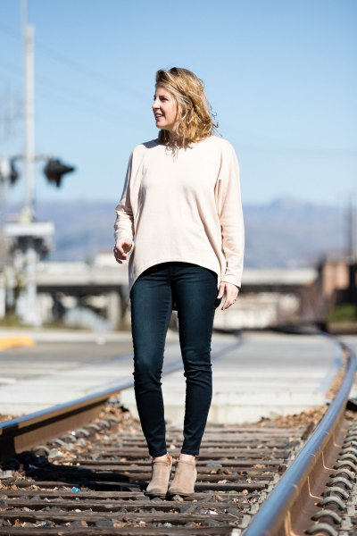 white casual fit sweater with dark blue features on slim jeans