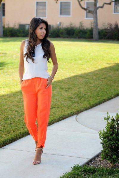 white sleeveless top with orange pull on jeans