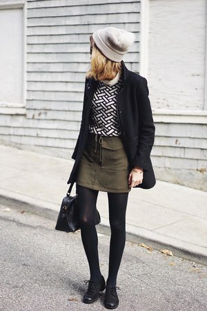 black and white patterned sweater with green mini-tie at the waist