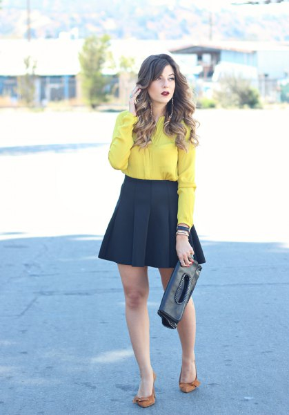 yellow button up shirt with black mini blown out and pleated skirt