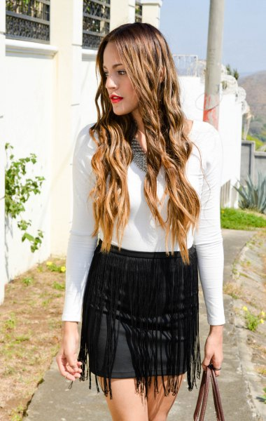 white long sleeve form tee with black mini bodycon fringed skirt