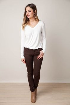 white long-sleeved tee with v-neck with brown jeans and ankle boots