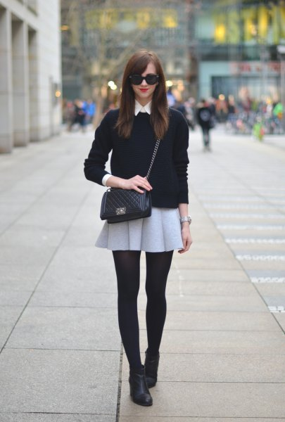 black sweater with light gray mini wool skirt