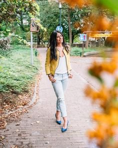 bomber jacket with white scoop neck vest and light blue jeans