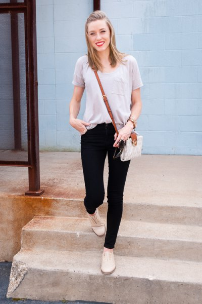 light gray tee with scoop neck with black skinny jeans and light yellow boots
