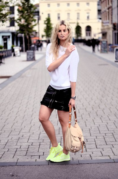 white sweater with black mini skirt and yellow sneakers