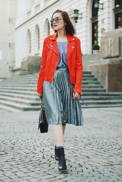 orange leather jacket with plaid blouse and silver pleated skirt