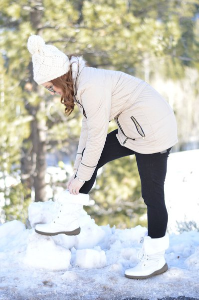 ivory front jacket with black leggings and white snow boots