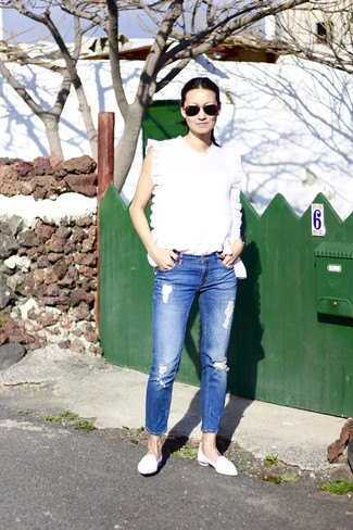 white sleeveless top with blue crop jeans and leather case