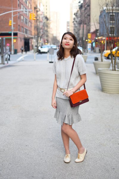 ivory short sleeve sweater with gray ruffle mini skirt and oxford shoes in white leather