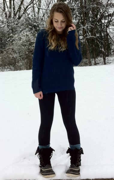 navy sweater with black leggings and snow boots