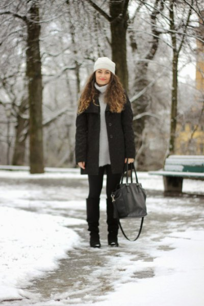 light gray sweater dress with down jacket and black snow boots in the knee