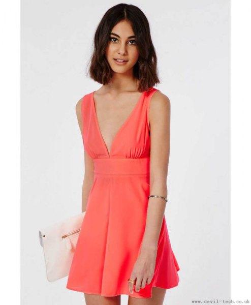 pink deep v-neck mini skater dress with white clutch bag