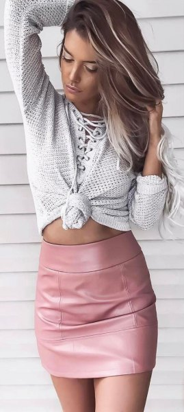 light gray knitted sweater with pink bodycon mini leather skirt