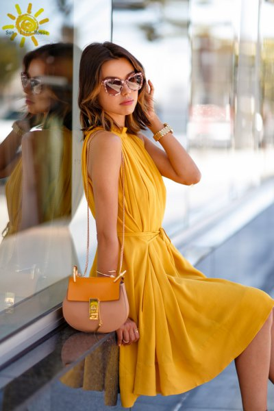 yellow sleeveless pleated midi pleated dress with pink handbag