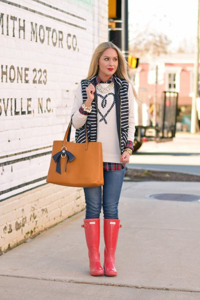 white embroidered sweater with blue jeans and orange rain boots in the knee