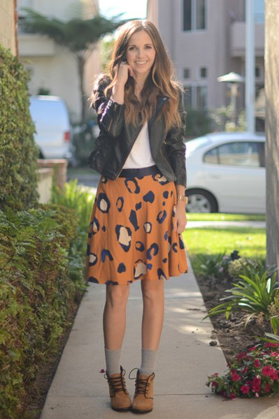 black leather jacket with orange printed mini skirt and lacing of ankle boots