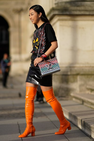 black tee and leather skirt with high boots in orange leather